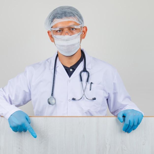 Młody Lekarz W Białym Fartuchu, Kapeluszu, Rękawiczkach, Pokazano Drewnianą Deskę Darmowe Zdjęcia
