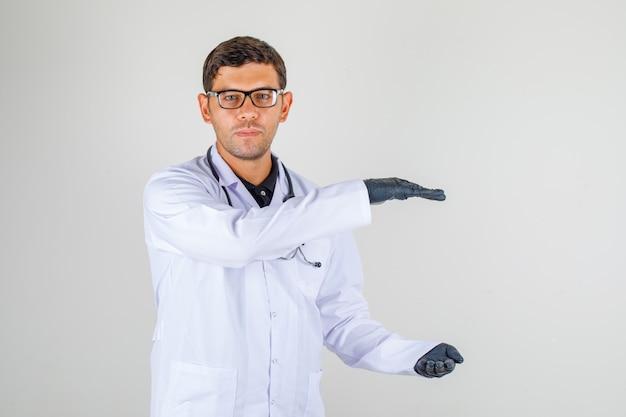 Młody Lekarz W Białym Fartuchu Ze Stetoskopem Przedstawiający Duży Znak Z Rękami Darmowe Zdjęcia