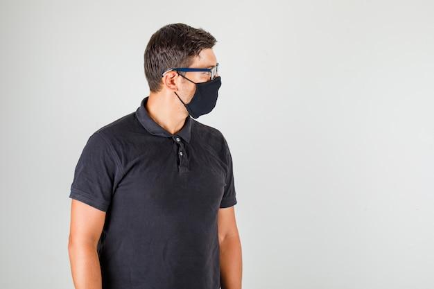 Młody Lekarz W Czarnej Koszulce Polo, Patrząc Na Jego Bok I Patrząc Uważnie Darmowe Zdjęcia