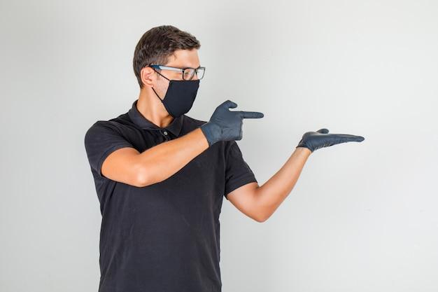 Młody Lekarz Wskazując Palcami W Prawo W Czarnej Koszulce Polo Darmowe Zdjęcia