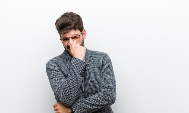 Młody Menedżer Czuje Się Zdegustowany, Trzymając Nos, Aby Uniknąć Wąchania Nieprzyjemnego I Nieprzyjemnego Smrodu Na Białej ścianie Premium Zdjęcia