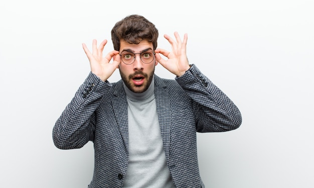 Młody menedżer czuje się zszokowany, zdziwiony i zaskoczony, trzymając okulary o zdumionym, niedowierzającym spojrzeniu na białej ścianie Premium Zdjęcia