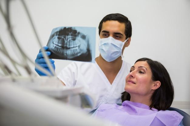 Młody Męski Dentysta Egzamininuje Promieniowanie Rentgenowskie Z żeńskim Pacjentem Darmowe Zdjęcia