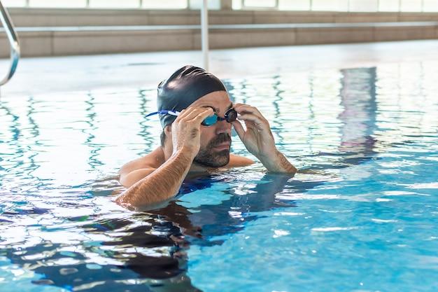 Młody Męski Pływak Przystosowywa Jego Gogle Dla Pływać W Olimpijskim Basenie Premium Zdjęcia