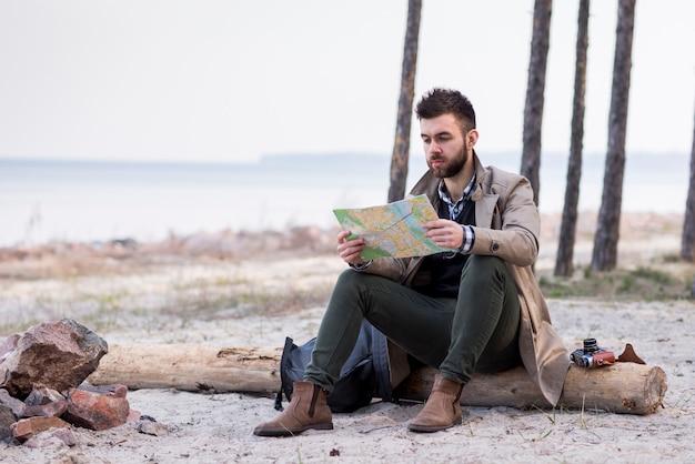 Młody męski wycieczkowicz siedzi na plaży nad belą patrzeje mapę Darmowe Zdjęcia