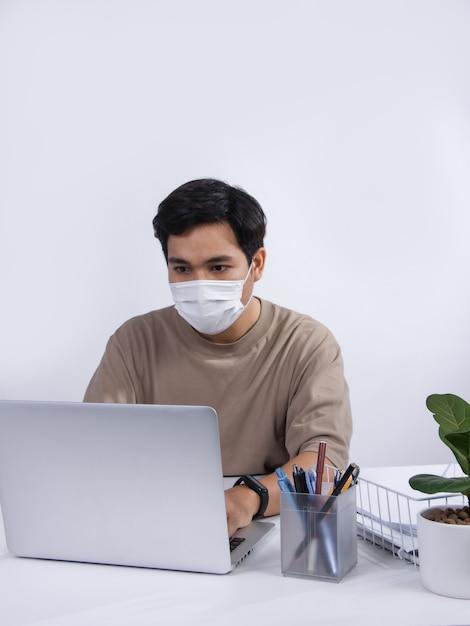 Młody Mężczyzna Azjatyckich Ubrany W Maskę Ochronną, Pracujący Projekt Na Swoim Komputerze Przenośnym W Biurze. Studio Strzał Na Białym Tle. Premium Zdjęcia