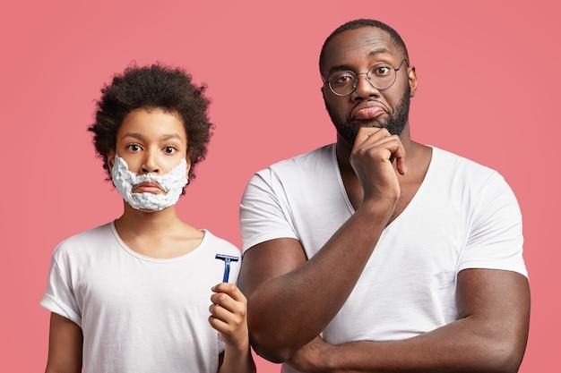 Młody Mężczyzna I Jego Syn Z Kręconymi Włosami, Trzymając Brzytwę Darmowe Zdjęcia