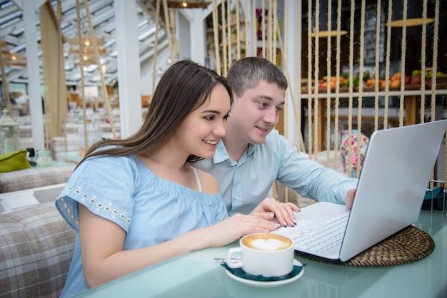 Młody mężczyzna i kobieta, patrząc na laptopa w kawiarni Premium Zdjęcia