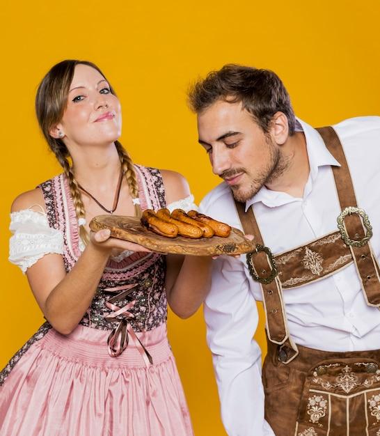 Młody mężczyzna i kobieta z grillowanymi kiełbasami Darmowe Zdjęcia