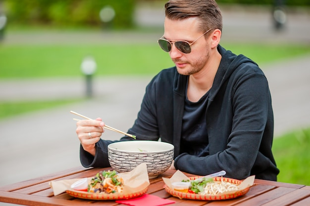 Młody mężczyzna jedzenie zabrać makaron na ulicy Premium Zdjęcia