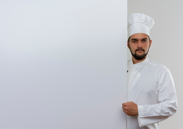 Młody Mężczyzna Kucharz W Mundurze Szefa Kuchni Stojący Za Białą ścianą Patrząc Z Zaciśniętą Pięścią Darmowe Zdjęcia