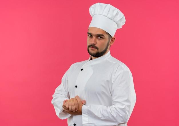 Młody Mężczyzna Kucharz W Mundurze Szefa Kuchni, Trzymając Ręce Razem, Patrząc Na Białym Tle Na Różowej Przestrzeni Darmowe Zdjęcia