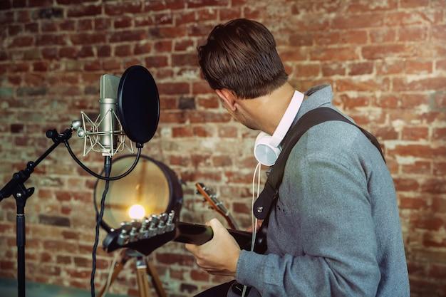Młody Mężczyzna Nagrywa Muzykę, Gra Na Gitarze I śpiewa W Domu Darmowe Zdjęcia