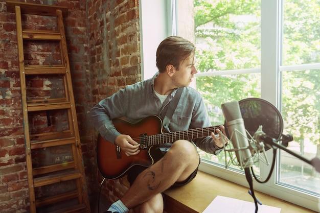 Młody Mężczyzna Nagrywa Teledysk, Lekcję Lub Piosenkę, Gra Na Gitarze Lub Prowadzi Internetowy Tutorial, Siedząc Na Poddaszu Lub W Domu Darmowe Zdjęcia