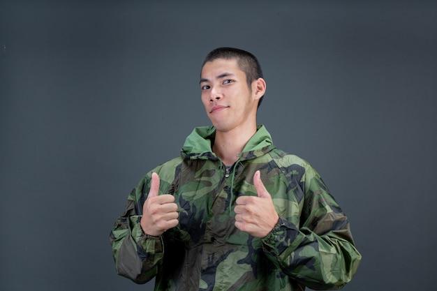 Młody Mężczyzna Nosi Kamuflażowy Płaszcz Przeciwdeszczowy I Pokazuje Różne Gesty. Darmowe Zdjęcia