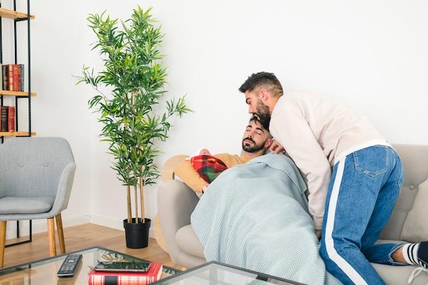 Młody mężczyzna patrząc na jego dziecko prowadzone przez chłopaka spanie na kanapie Darmowe Zdjęcia