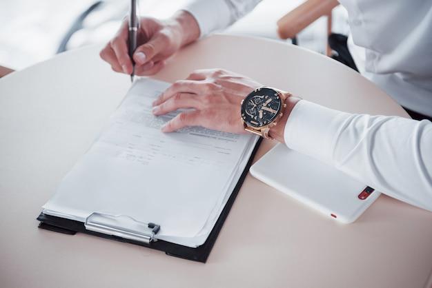 Młody Mężczyzna Podpisuje Dokumenty W Biurze, Sprzedaż Udana. Premium Zdjęcia