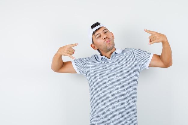 Młody Mężczyzna Robi Symbol Rocka W Koszulce I Czapce I Wygląda Fajnie Darmowe Zdjęcia