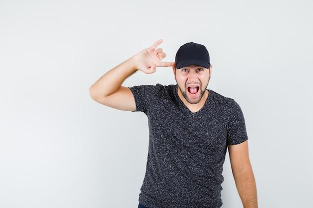 Młody Mężczyzna Robi Symbol Rocka Z Palcem Na Skroniach W T-shirt I Czapce I Wygląda Szalenie Darmowe Zdjęcia