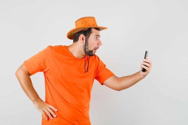 Młody Mężczyzna Rozmawia Na Czacie Wideo W Pomarańczowej Koszulce, Kapeluszu I Patrząc Zszokowany, Widok Z Przodu. Darmowe Zdjęcia