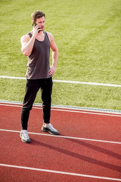 Młody mężczyzna sportowiec stojący na torze wyścigowym rozmawia przez telefon komórkowy Darmowe Zdjęcia