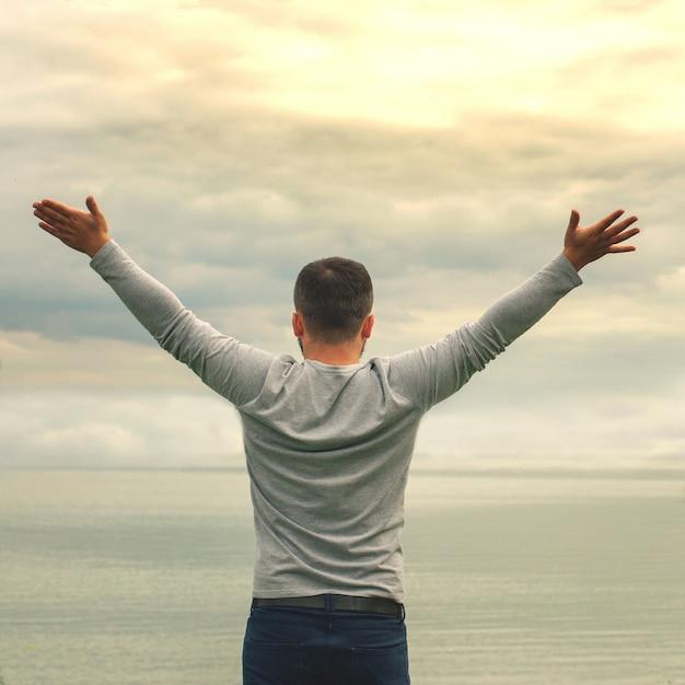 Młody mężczyzna stoi na brzegu. widok z tyłu. zajęcia jogi. podniósł ręce. wolność i osiągnięcia. Premium Zdjęcia