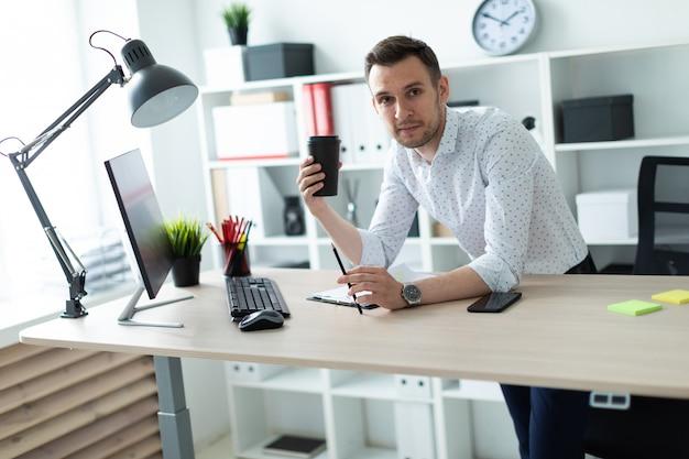 Młody Mężczyzna Stoi Przy Stole W Biurze, Trzymając Ołówek I Szklankę Kawy. Młody Człowiek Pracuje Z Dokumentami I Komputerem. Premium Zdjęcia