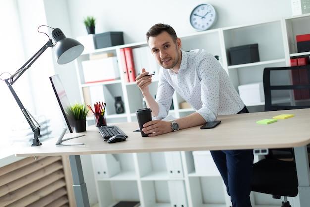 Młody Mężczyzna Stoi Przy Stole W Biurze, Trzymając Ołówek I Szklankę Kawy. Premium Zdjęcia