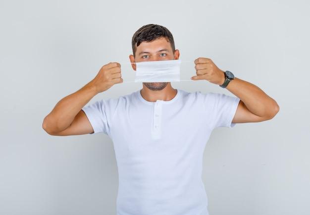 Młody Mężczyzna Trzyma Maskę Medyczną Na Ustach W Białej Koszulce, Widok Z Przodu. Darmowe Zdjęcia