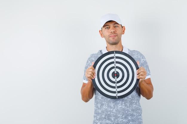 Młody Mężczyzna Trzyma Tarczę W T-shirt I Czapkę I Wygląda Rozsądnie Darmowe Zdjęcia