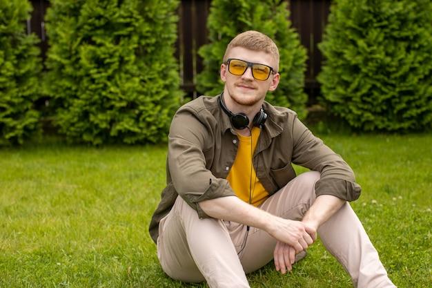 Młody Mężczyzna Ubrany Niedbale W żółtych Okularach Siedzi Na Zielonej Trawie Ze Słuchawkami Na Szyi, Patrząc W Zamyśleniu Na Zielonym Tle. Premium Zdjęcia