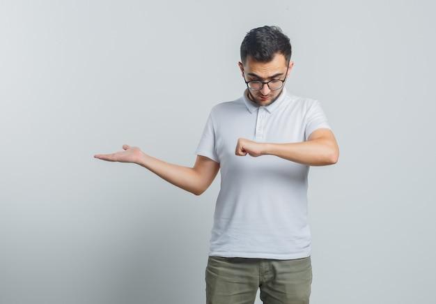 Młody Mężczyzna Udający, że Patrzy Na Zegarek Na Nadgarstku, Pokazujący Coś W Białej Koszulce, Spodniach I Wyglądający Na Skupionego Darmowe Zdjęcia
