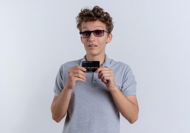 Młody Mężczyzna W Czarnych Okularach Na Sobie Szarą Koszulkę Polo Pokazując Kartę Kredytową Zaskoczony Stojąc Nad Białą ścianą Darmowe Zdjęcia