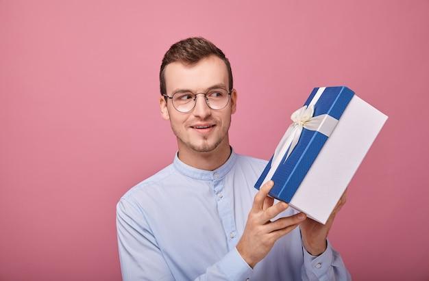 Młody mężczyzna w delikatnie niebieskiej koszuli ze zdziwieniem Premium Zdjęcia