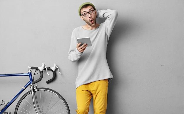Młody Mężczyzna W Modnych Ciuchach, Robiąc Zakupy Online, Używając Tabletu, Jest Zaskoczony Darmowe Zdjęcia