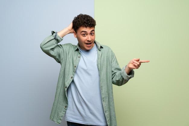 Młody mężczyzna w niebiesko-zielony palec wskazujący z boku i przedstawiający produkt Premium Zdjęcia