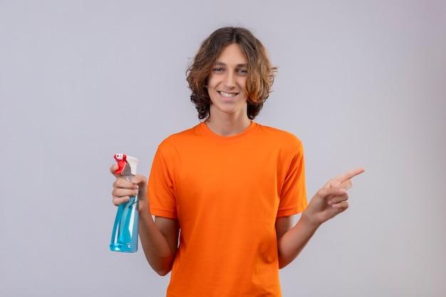 Młody Mężczyzna W Pomarańczowej Koszulce Gospodarstwa Spray Do Czyszczenia, Uśmiechając Się Radośnie Patrząc Na Kamerę, Wskazując Na Bok Stojący Na Białym Tle Darmowe Zdjęcia