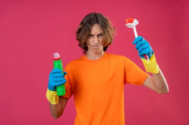 Młody Mężczyzna W Pomarańczowej Koszulce W Gumowych Rękawiczkach Trzymający Butelkę środków Czyszczących I Szczoteczka Do Szorowania Patrząc Na Kamerę Niezadowolony Z Zmarszczonej Twarzy Stojącej Na Różowym Tle Darmowe Zdjęcia