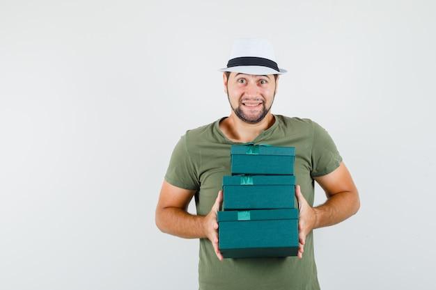 Młody Mężczyzna W Zielonej Koszulce I Kapeluszu, Trzymając Obecne Pudełka I Patrząc Optymistycznie Darmowe Zdjęcia