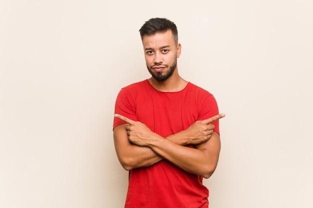 Młody Mężczyzna Z Azji Południowej Wskazuje Na Boki, Próbuje Wybrać Jedną Z Dwóch Opcji. Premium Zdjęcia