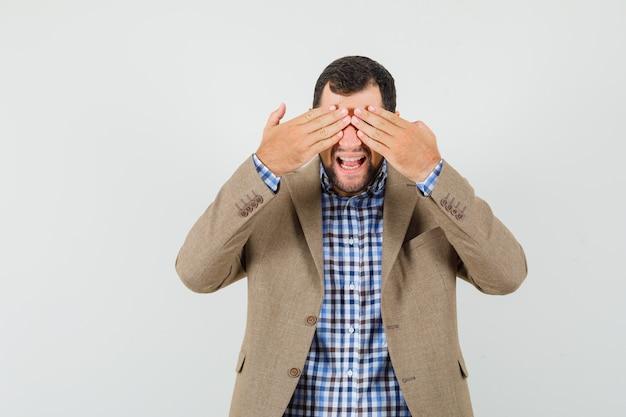 Młody Mężczyzna Zakrywający Oczy Rękami W Koszuli, Kurtce I Patrząc Podekscytowany, Widok Z Przodu. Darmowe Zdjęcia