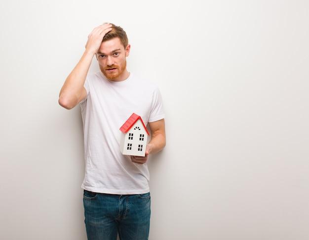 Młody mężczyzna zmartwiony i przytłoczony. trzymanie modelu domu. Premium Zdjęcia