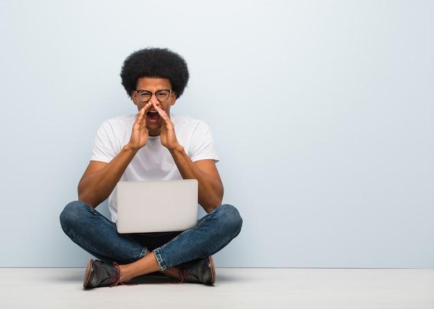 Młody Murzyn Siedzący Na Podłodze Z Laptopem Krzyczy Coś Szczęśliwego Do Przodu Premium Zdjęcia