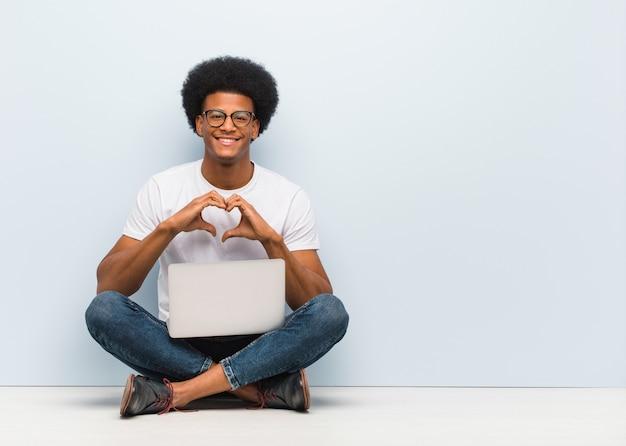 Młody murzyn siedzący podłogę z laptopem robi kształt serca z rąk Premium Zdjęcia