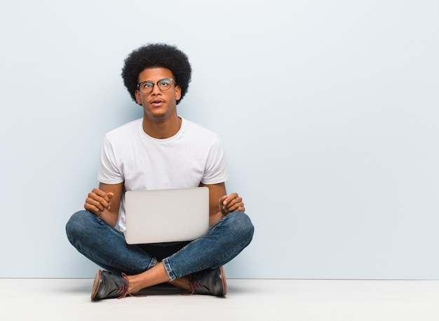 Młody Murzyn Siedzi Na Podłodze Z Laptopem Zmęczony I Znudzony Premium Zdjęcia
