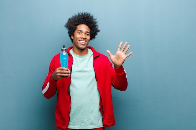 Młody murzyn z napojem sportowym na ścianie niebieski nieczysty Premium Zdjęcia