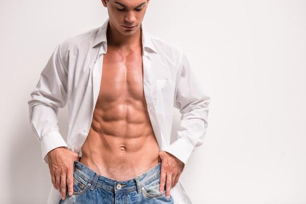 Młody muskularny mężczyzna w otwartej koszuli Premium Zdjęcia