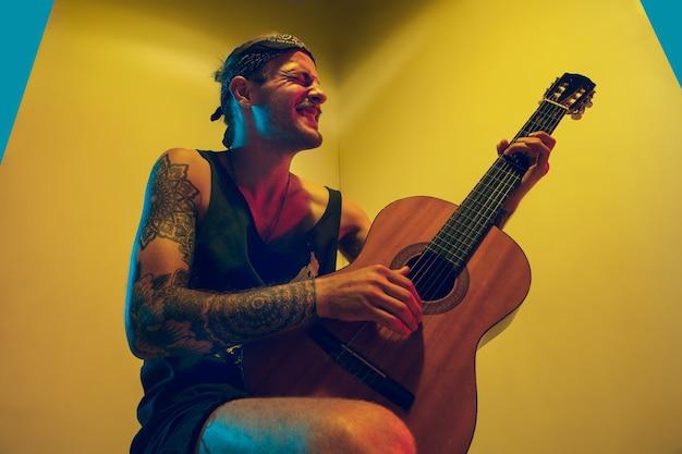Młody Muzyk Wykonujący Na Kolorowej ścianie W świetle Neonu Darmowe Zdjęcia