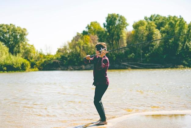 Młody nastolatek rybak w dorywczo łowienie ryb na brzegu rzeki z prętem w letni dzień Premium Zdjęcia