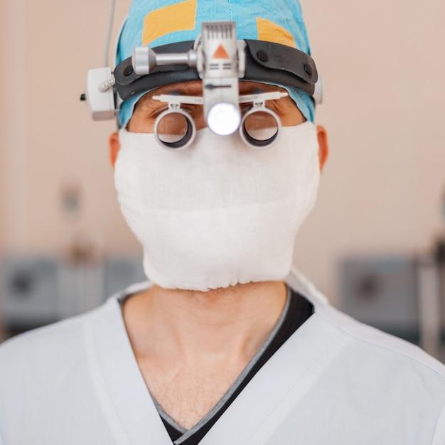 Młody Neurochirurg W Masce Medycznej Z Profesjonalnymi Lupami Z Lupami Binarnymi Do Mikrochirurgii. Instrumenty Chirurgiczne Premium Zdjęcia
